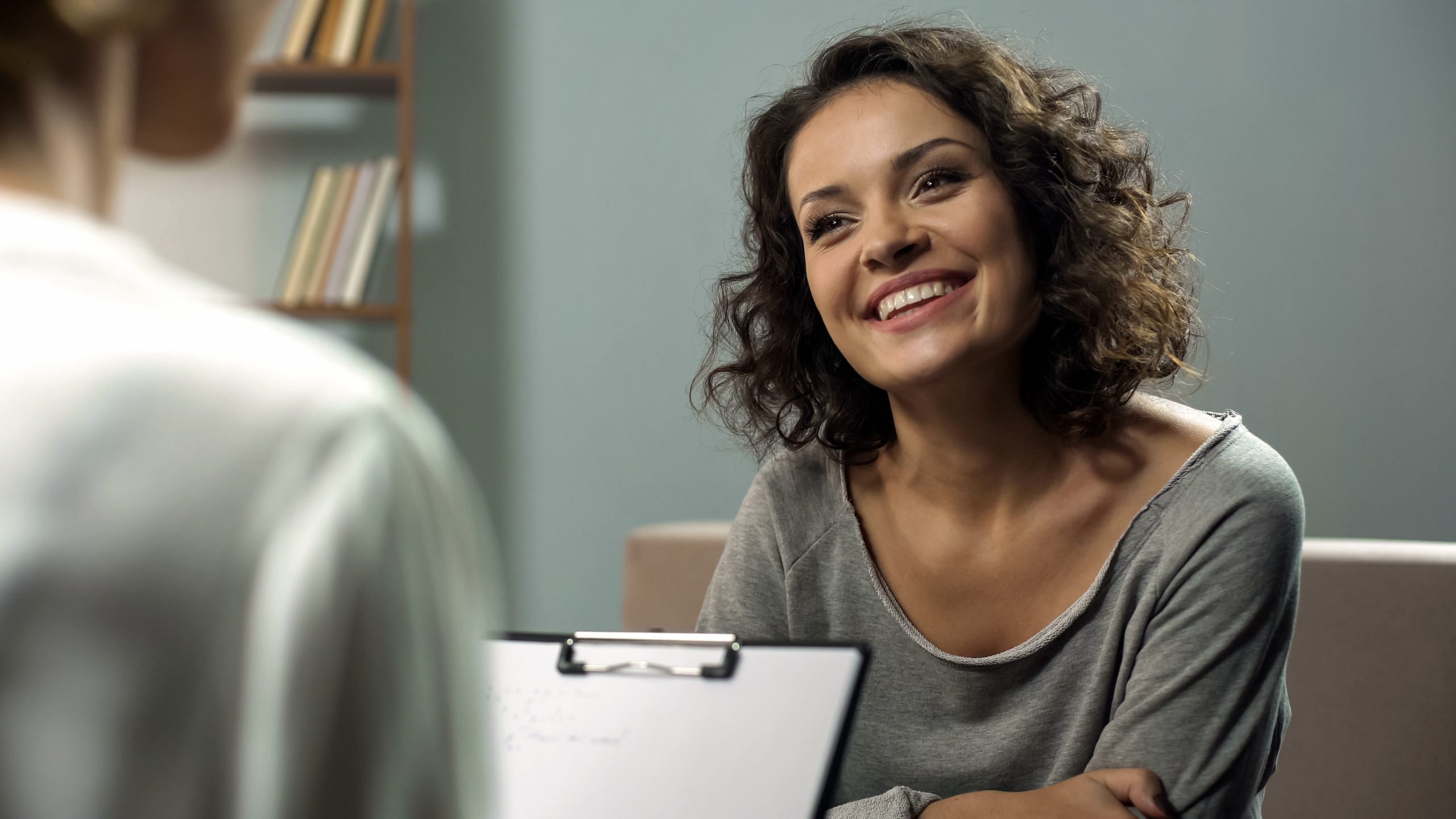 Young woman smiles and talks with a women's health specialist at her appointment