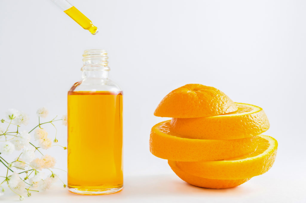 orange and bottle of vitamin C serum with dropper