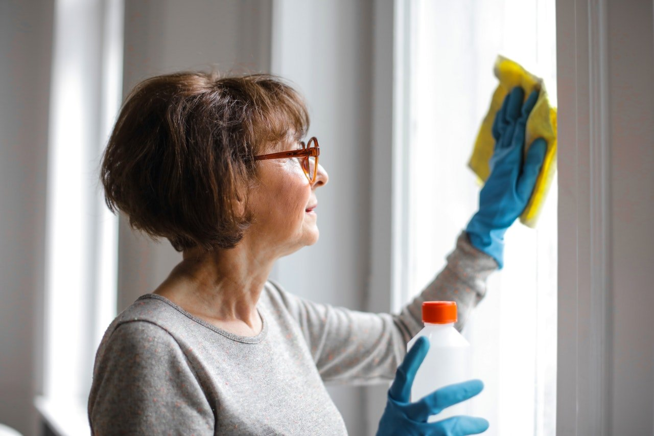 woman washes a sunny window to clean her home for spring